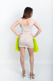 Beautiful young leggy brunette in a little gray cocktail dress full height. holding shopping bags, she goes shopping Stock Photography