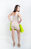 Beautiful young leggy brunette in a little gray cocktail dress full height. holding shopping bags, she goes shopping Stock Photos