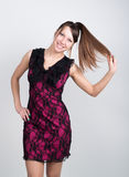 Beautiful young leggy brunette in a little red dress pulls his hair Royalty Free Stock Image
