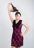 Beautiful young leggy brunette in a little red dress pulls his hair Royalty Free Stock Photo