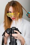 Beautiful young leggy redhaired model looks pictures on the camera, hairdresser does a hairstyle. two girls with glasses Royalty Free Stock Image