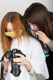 Beautiful young leggy redhaired model looks pictures on the camera, hairdresser does a hairstyle. two girls with glasses Stock Photography