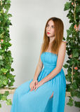 Beautiful young leggy redhaired woman in a long blue dress on a swing, wooden swing suspended from a rope hemp, rope. Wrapped vine and ivy Royalty Free Stock Photography
