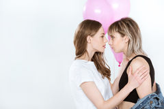 Beautiful young lesbian couple holding pink balloons and looking at each other stock image