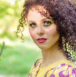 Beautiful young little curly-headed girl with makeup in the summer sun the day sitting on the street Royalty Free Stock Photography