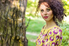Beautiful young little curly-headed girl with makeup in the summer sun the day sitting on the street Royalty Free Stock Image