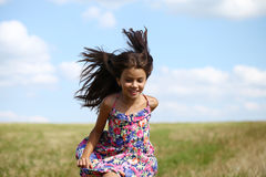 Beautiful young little girl running summer field Stock Images