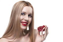 Beautiful young long haired red lips blonde girl holds a half of. Pomegranate in her hands and smiles. Naked shoulders. Isolated on white. Copy space. Beauty Royalty Free Stock Photos