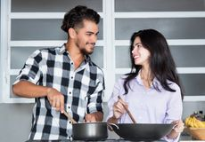 Beautiful young love couple cooking at kitchen Stock Images