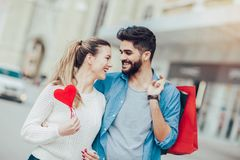 Young lovers holding a big red heart and shopping bag. Beautiful young lovers holding a big red heart and shopping bag Stock Images
