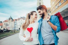 Beautiful young lovers holding a big red heart. And shopping bag Stock Photo