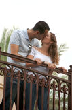 Beautiful young lovers kissing on outdoor balcony. Beautiful young lovers holding on to balcony railing and kissing. shot from low angle with palm trees in back Stock Images