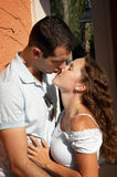 Beautiful young lovers about to kiss in the aftern. Beautiful young lovers holding each other about to kiss outdoors in the hot afternoon sun in tropical setting Royalty Free Stock Photo