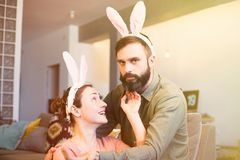 Beautiful young loving couple bonding to each other with pink rabbit ears on head. Happy family preparing for Easter. Beautiful young loving couple bonding to stock photo
