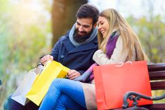 Beautiful young loving couple carrying bags and enjoying together shopping. Beautiful young loving couple carrying bags and enjoying together holiday shopping. A Royalty Free Stock Photo