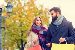 Beautiful young loving couple carrying bags and enjoying together shopping. Beautiful young loving couple carrying bags and enjoying together holiday shopping. A Stock Photo