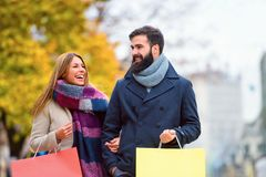 Beautiful young loving couple carrying bags and enjoying together shopping. Beautiful young loving couple carrying bags and enjoying together holiday shopping. A Royalty Free Stock Image