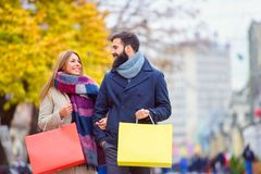Beautiful young loving couple carrying bags and enjoying together shopping. Beautiful young loving couple carrying bags and enjoying together holiday shopping. A Stock Photos