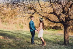 Beautiful young loving couple holding each other hands. Love and tenderness. Beautiful young loving couple holding each other hands in blossom spring garden Royalty Free Stock Image