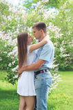 Beautiful young loving couple hugging in blooming garden Royalty Free Stock Image
