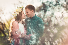 Beautiful young loving couple looking at eath other and smiling. Love and tenderness. Beautiful young loving couple looking at eath other and smiling in blossom Stock Photo