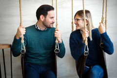 Beautiful young loving couple relaxing in swing Stock Photography