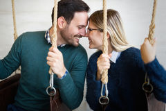 Beautiful young loving couple relaxing in swing Royalty Free Stock Photos
