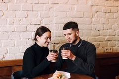 Beautiful young loving couple sitting in a cafe royalty free stock photos