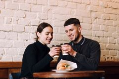 Beautiful young loving couple sitting in a cafe stock images