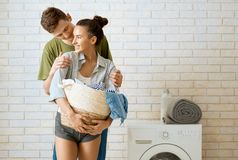 Loving couple is doing laundry. Beautiful young loving couple is smiling while doing laundry at home stock photo