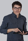 Beautiful young man in glasses and tablet Royalty Free Stock Photo