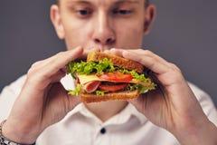 Young man looking at a fresh burger. Beautiful Young man looking at a fresh burger Royalty Free Stock Photos