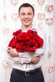 Beautiful young man  in love with a bouquet of flowers. Valentine's Day. Royalty Free Stock Photography