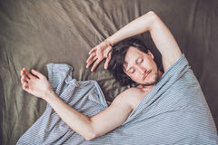 Beautiful young man lying down in bed and sleeping, top view. Do not get enough sleep concept Royalty Free Stock Image
