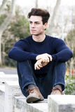 Beautiful young man model, trendy outfit hairstyle. Fabulous and beautiful model with trendy hairstyle and modern look sitting on a wall in a park in the center Stock Photos