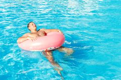 Beautiful young man relaxing in pool. vacation concept with space for text. Top view stock photography