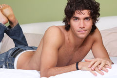 Beautiful young man shirtless on bed Stock Photography