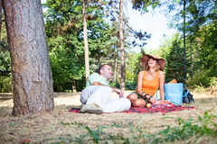 Beautiful young man and woman on picnic in forest royalty free stock photography