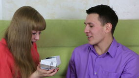 Beautiful young man with woman sitting on couch. Guy gives the girl a gift. stock footage