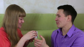 Beautiful young man with woman sitting on couch. Guy gives the girl a gift. Beautiful young man with woman sitting on the couch. Guy gives the girl a gift stock footage