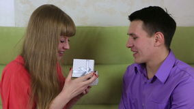 Beautiful young man with woman sitting on couch. Guy gives the girl a gift. Beautiful young man with woman sitting on the couch. Guy gives the girl a gift stock video