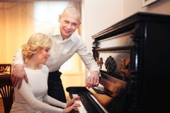 Beautiful young man and woman sitting and playing the piano Stock Photography