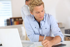 Beautiful young man writing in office royalty free stock images