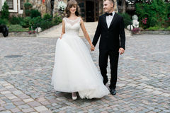Beautiful young married couple walking and holding hands.  Royalty Free Stock Photography