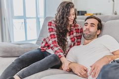 Beautiful young married couple is watching tv with joy. They are sitting on sofa and embracing. The man is holding the stock photography