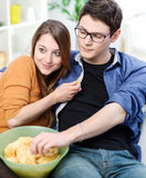 Beautiful young married looking for tv and eating on a sofa at a Stock Photography