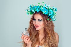 Woman with floral headband crown giving perfume bottle royalty free stock photos