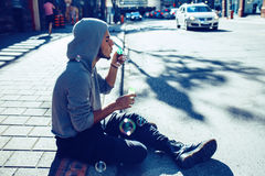 Beautiful young middle eastern appearance man with beard in hoodie blowing bubbles Royalty Free Stock Images
