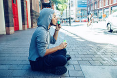 Beautiful young middle eastern appearance man with beard in hoodie blowing bubbles Royalty Free Stock Photos