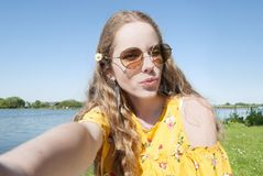 Beautiful young millennial girl, taking selfie pcture with cell phone camera stock photos